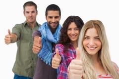 Φίλοι που δίνουν τους αντίχειρες επάνω σε μια σειρά Στοκ εικόνα με δικαίωμα ελεύθερης χρήσης