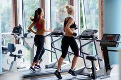 Φίλοι που ασκούν treadmill στη φωτεινή σύγχρονη γυμναστική Στοκ Εικόνες