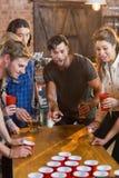 Φίλοι που εξετάζουν τη σφαίρα ενώ μπύρα παιχνιδιού ατόμων pong στο φραγμό Στοκ φωτογραφία με δικαίωμα ελεύθερης χρήσης