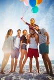 Φίλοι που θέτουν με το μπαλόνι στην άμμο Στοκ φωτογραφία με δικαίωμα ελεύθερης χρήσης