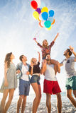 Φίλοι που θέτουν με το μπαλόνι στην άμμο Στοκ Εικόνα