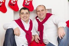 Φίλοι που κάθονται κοντά στην εστία Χριστουγέννων Στοκ Φωτογραφία