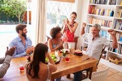 Φίλοι που κάθονται σε έναν να δειπνήσει πίνακα που γιορτάζει γενέθλια Στοκ Εικόνες