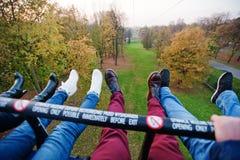 Φίλοι που κάθονται στο τελεφερίκ και που παρουσιάζουν πόδια τους με το sho Στοκ Φωτογραφίες