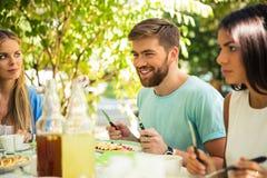 Φίλοι που κάθονται στο υπαίθριο εστιατόριο Στοκ Φωτογραφίες
