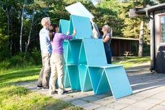 Φίλοι που κάνουν την πυραμίδα με τις ξύλινες σανίδες σε Patio στο δάσος Στοκ Εικόνες