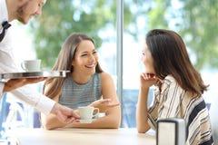 Φίλοι που μιλούν σε έναν φραγμό με την εξυπηρέτηση σερβιτόρων Στοκ Φωτογραφία