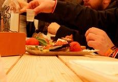 Φίλοι που πίνουν και που τρώνε τη διασκέδαση Στοκ Εικόνες