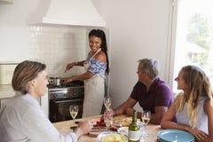 Φίλοι που πίνουν το κρασί στην κουζίνα ενώ η γυναίκα προετοιμάζει τα τρόφιμα Στοκ φωτογραφία με δικαίωμα ελεύθερης χρήσης