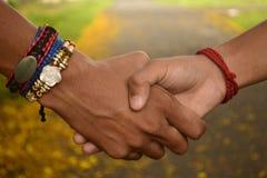 Φίλοι που τινάζουν τα χέρια Rakhi ζωνών φιλίας Στοκ Φωτογραφίες