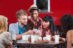 Φίλοι που τρώνε και που εξετάζουν το τηλέφωνο στοκ εικόνα