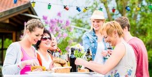 Φίλοι που τρώνε bbq το λουκάνικο και το κρέας Στοκ εικόνα με δικαίωμα ελεύθερης χρήσης