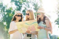 Φίλοι που ψάχνουν τις κατευθύνσεις σε έναν χάρτη στις καλοκαιρινές διακοπές στοκ εικόνες
