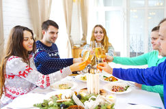 Φίλοι που ψήνουν με τη σαμπάνια ενώ έχοντας το γεύμα Χριστουγέννων στοκ φωτογραφία