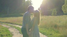 Φίλος και φίλη, αγαπώντας ζεύγος που περπατούν και που φιλούν στο ηλιοβασίλεμα στα αγροτικά mestres στη φύση απόθεμα βίντεο