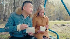Φίλος και φίλη που τρώνε τα ασιατικά τρόφιμα φιλμ μικρού μήκους