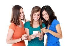 Φίλος νέων κοριτσιών που χρησιμοποιεί τα κινητά τηλέφωνα Στοκ Εικόνες