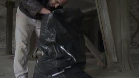 Φαλακρές άστεγες αναζητήσεις κάτι στην τσάντα απορριμάτων φιλμ μικρού μήκους