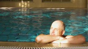 Φαλακρή ονειροπόλος χαλάρωση ατόμων στην πισίνα με το φρέσκο μπλε νερό απόθεμα βίντεο