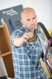 Φαλακρό άτομο που επισκευάζει το ποδήλατο στο εργαστήριο Στοκ Εικόνες