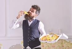 Φαλλοκράτης στα κλασικά ενδύματα πεινασμένα, στο εύθυμο πρόσωπο, φέτα δαγκωμάτων της πίτσας, κατανάλωση, άσπρο υπόβαθρο Παράδοση  στοκ φωτογραφίες