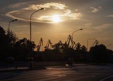 Φανάρια ακρών του δρόμου και λιμενικοί γερανοί ενάντια στο σκηνικό ενός ηλιοβασιλέματος με τα όμορφα σύννεφα σε Klaipeda, Λιθουαν στοκ φωτογραφία με δικαίωμα ελεύθερης χρήσης