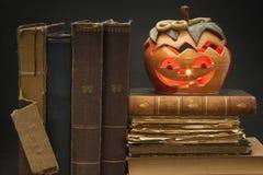 Φανάρι κολοκύθας για αποκριές και τα παλαιά βιβλία μαγισσών Κεφάλι που χαράζεται από μια κολοκύθα σε αποκριές Παράδοση κολοκύθας Στοκ Εικόνα