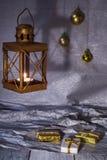 Φανάρι με τις διακοσμήσεις κεριών και Χριστουγέννων σε ένα ασημένιο υπόβαθρο Στοκ Φωτογραφία