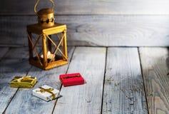 Φανάρι με τις διακοσμήσεις κεριών και Χριστουγέννων σε μια άσπρη ξύλινη επιφάνεια Στοκ Φωτογραφία