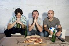 Φανατικοί οπαδοί ποδοσφαίρου φίλων που προσέχουν αγώνας TV με τα μπουκάλια μπύρας και την πίτσα που υφίσταται την πίεση Στοκ Εικόνα