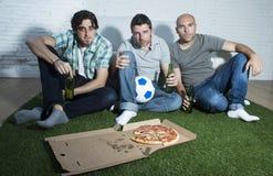 Φανατικοί οπαδοί ποδοσφαίρου φίλων που προσέχουν αγώνας TV με τα μπουκάλια μπύρας και την πίτσα που υφίσταται την πίεση Στοκ εικόνα με δικαίωμα ελεύθερης χρήσης