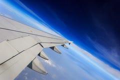 Φανείτε έξω το παράθυρο αεροπλάνων Δείτε τις άσπρα συστάδες σύννεφων και το φτερό του αεροπλάνου, επάνω κλίση στοκ εικόνα με δικαίωμα ελεύθερης χρήσης