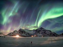 Φανταστικά borealis αυγής πέρα από το χιονώδες βουνό με τη στάση ατόμων στοκ εικόνα με δικαίωμα ελεύθερης χρήσης