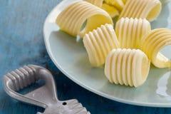 Φανταχτερές μπούκλες του φρέσκου αγροτικού βουτύρου σε ένα πιάτο Στοκ Φωτογραφίες