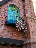 Φανταχτερή λεπτομέρεια σπιτιών τούβλου με το μπαλκόνι και το γεράνι Στοκ Εικόνες