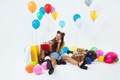 Φανταχτερό κορίτσι, που τοποθετεί τις κλήσεις γενεθλίων που κάθονται στο καθιστικό Στοκ φωτογραφία με δικαίωμα ελεύθερης χρήσης