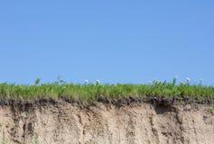 Φαράγγι ή gully που κόβεται με το χώμα, τη χλόη και το μπλε ουρανό στοκ φωτογραφία