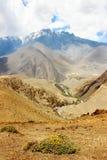 Φαράγγι στα βουνά Himalayan στο υπόβαθρο των χιονωδών αιχμών και του μπλε ουρανού με τα σύννεφα Νεπάλ Ανώτερο μάστανγκ ` βασίλειω Στοκ φωτογραφία με δικαίωμα ελεύθερης χρήσης