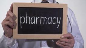 Φαρμακείο που γράφεται στον πίνακα στα χέρια γιατρών, βιομηχανία φαρμάκων, φάρμακα απόθεμα βίντεο