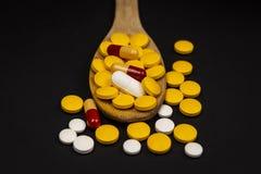 Φαρμακευτικά χάπια ιατρικής, στο ξύλινο κουτάλι στο μαύρο υπόβαθρο στοκ εικόνες