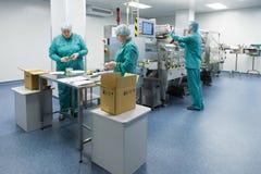 Φαρμακευτικοί βιομηχανικοί εργάτες στο αποστειρωμένο περιβάλλον στοκ εικόνα