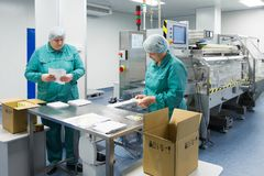 Φαρμακευτικοί βιομηχανικοί εργάτες στο αποστειρωμένο περιβάλλον στοκ φωτογραφία με δικαίωμα ελεύθερης χρήσης