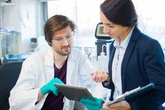 Φαρμακευτικός επιστήμονας που εξετάζει τις πληροφορίες για την ταμπλέτα στοκ φωτογραφίες