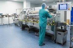 Φαρμακευτικός εργαζόμενος ατόμων εργοστασίων στη λειτουργούσα γραμμή παραγωγής προστατευτικής ενδυμασίας στο αποστειρωμένο περιβά στοκ εικόνες με δικαίωμα ελεύθερης χρήσης