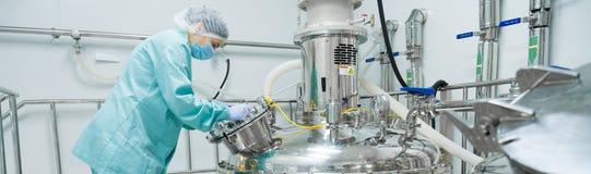 Φαρμακευτικός εργαζόμενος γυναικών εργοστασίων στη λειτουργούσα γραμμή παραγωγής προστατευτικής ενδυμασίας στο αποστειρωμένο περι στοκ εικόνες