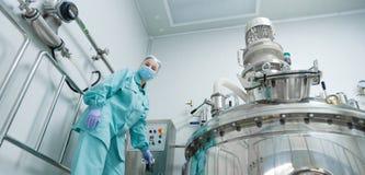 Φαρμακευτικός εργαζόμενος γυναικών εργοστασίων στη λειτουργούσα γραμμή παραγωγής προστατευτικής ενδυμασίας στο αποστειρωμένο περι στοκ εικόνες με δικαίωμα ελεύθερης χρήσης