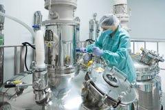 Φαρμακευτικός εργαζόμενος γυναικών εργοστασίων στη λειτουργούσα γραμμή παραγωγής προστατευτικής ενδυμασίας στο αποστειρωμένο περι στοκ φωτογραφίες