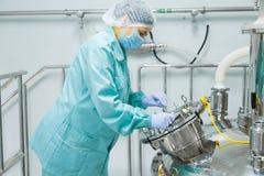 Φαρμακευτικός εργαζόμενος γυναικών εργοστασίων στη λειτουργούσα γραμμή παραγωγής προστατευτικής ενδυμασίας στο αποστειρωμένο περι στοκ εικόνα