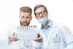 Φαρμακοποιοί ατόμων στα παλτά εργαστηρίων που κρατούν τους σωλήνες δοκιμής και που χαμογελούν στη κάμερα Στοκ εικόνες με δικαίωμα ελεύθερης χρήσης
