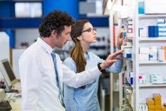 Φαρμακοποιοί που ελέγχουν τα φάρμακα στο ράφι στο φαρμακείο στοκ εικόνες